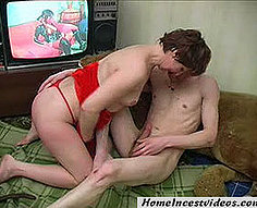 Un fils aux cheveux longs et sa mère en rouge regardent le porno ensemble