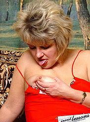 Mère en robe rouge et bas noirs suce la bite de son fils